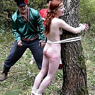 Tearful redhead tied to a tree in the forest and brutally caned - severe bruises and stripes